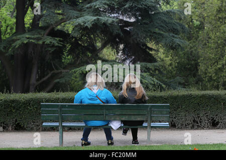 Two girls on a bench. - Stock Photo