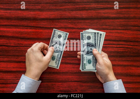 Hands counting money on a desk - Stock Photo