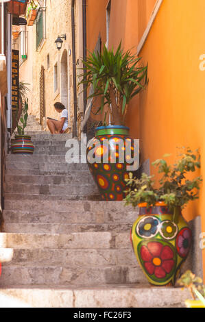 Taormina Sicily, A man reads alone in a narrow street in the old town area of Taormina, Sicily. - Stock Photo