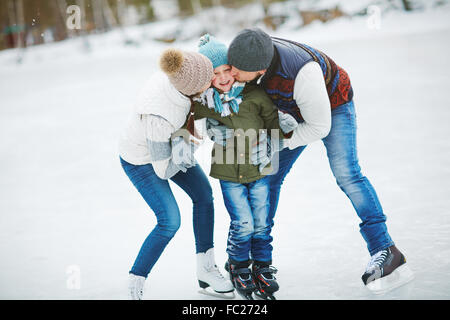 Happy parents kissing their cute son on skating rink - Stock Photo