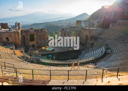 Taormina Greek theatre, view at sunset of people walking across the ancient Greek theatre (Teatro Greco) Taormina, - Stock Photo