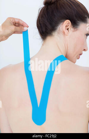 Physiotherapist applying blue kinesio tape to patients back - Stock Photo