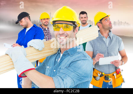 Composite image of carpenter wearing hardhat and glasses while carrying wooden planks - Stock Photo