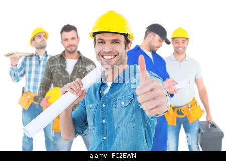 Composite image of architect holding blueprint while gesturing thumbs up - Stock Photo