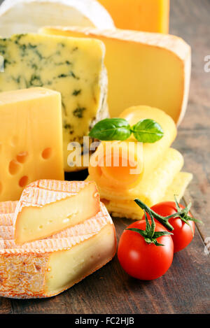 Different sorts of cheese on kitchen table. - Stock Photo