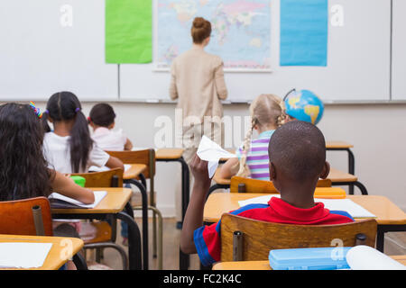 Naughty pupil about to throw paper airplane in class - Stock Photo