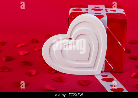 Red Holidays gift and heart on red background. Valentines day background. - Stock Photo