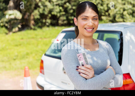 happy learner driver holding her driver's license - Stock Photo