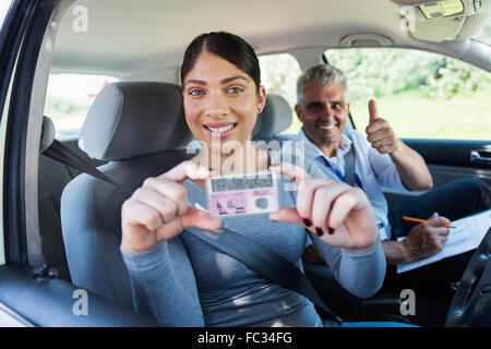 pretty woman has passed her driving test and holding driver's license - Stock Photo