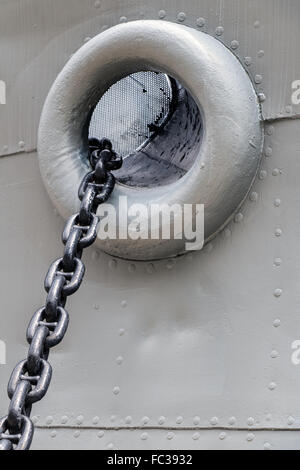 chain in the anchor hole - Stock Photo