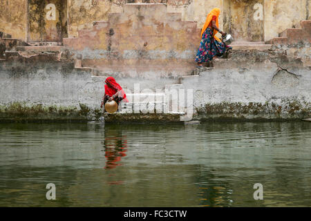Two Local Women in the stepwells of Chand Baori or Panna Meena Ka Kund, in Jaipur, India. - Stock Photo