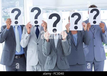 Business colleagues hiding their face with question mark sign - Stock Photo