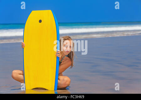 Happy girl - young surfer with bodyboard has fun on sea sand beach with waves. Stock Photo