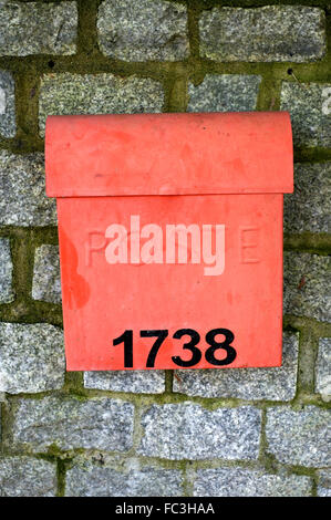 Red metal mailbox on a natural stone wall - Stock Photo