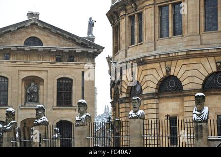The Roman emperors' heads outside the Sheldonian Theatre in Oxford with a light covering of snow. - Stock Photo