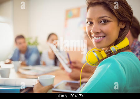 Smiling businesswoman with yellow headphones in a meeting - Stock Photo