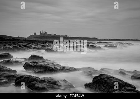 Monochrome long exposure capture of Dunstanburgh Castle Northumberland - Stock Photo