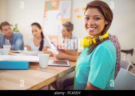 Pretty casual businesswoman with yellow headphones - Stock Photo