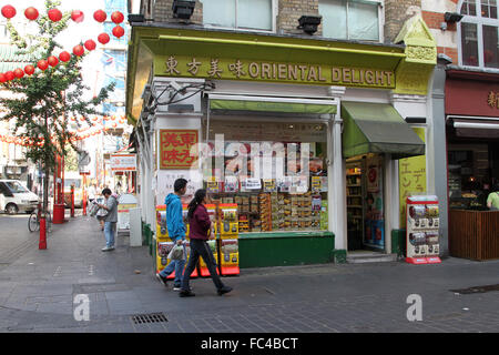 People walking past Chinese shop in Chinatown, W1, London - Stock Photo