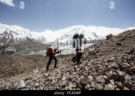 A couple of mountaineers in the approach to advanced basecamp of Peak Lenin - Stock Photo
