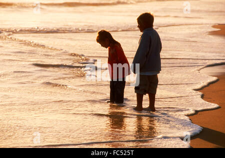 Boy and girl standing in shallow shore waves at sunset - Stock Photo