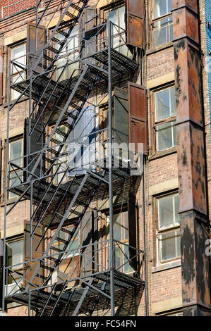 Fire escape on an old brick wall building with its rusted metal shutters on Bleeker Street in Soho, Manhattan, New - Stock Photo