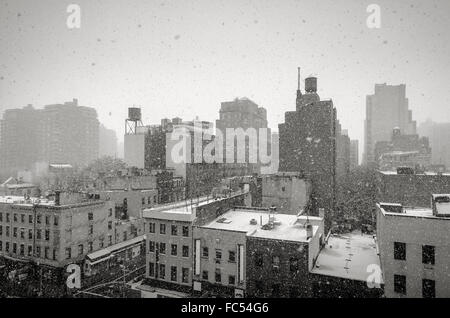 Winter in New York Chelsea neighborhood. Black & White View of New York City during a snowfall, with rooftops and - Stock Photo