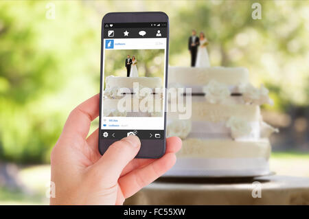 Composite image of female hand holding a smartphone - Stock Photo