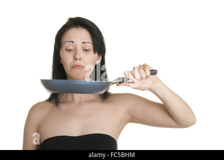 Surprised young woman with frying pan - Stock Photo