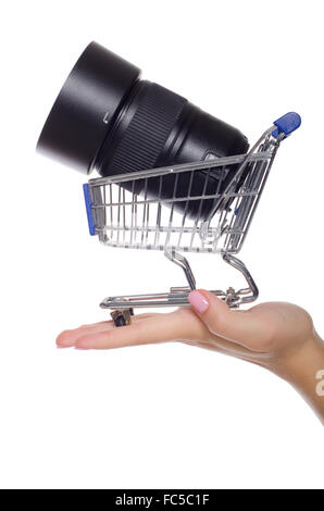 Camera lens in shopping trolley on the palm - Stock Photo