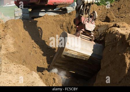Excavators encounters hard ground - Stock Photo