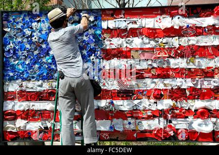 Man stapling object on recycled American flag (by artist Todd Kundla), 2015 Cherry Creek Arts Festival, Denver, - Stock Photo