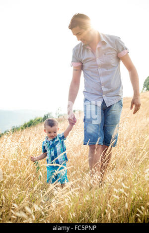 Man and Young Boy Walking Through Field - Stock Photo