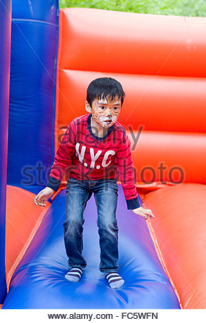 Little boy on the bouncy castle - Stock Photo