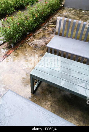 Concrete bench set with rain for relaxing in the park. - Stock Photo