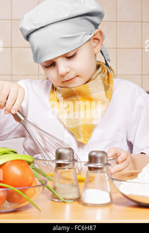 Little cook whisking eggs in a bowl - Stock Photo