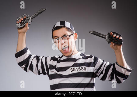 Young prisoner holding knifes against gray - Stock Photo