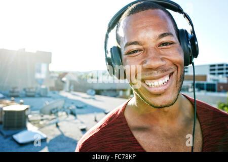African American man listening to headphones on urban rooftop - Stock Photo