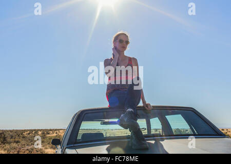 Caucasian woman sitting on roof of car in desert - Stock Photo