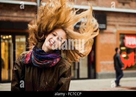 Caucasian woman tossing hair outdoors - Stock Photo