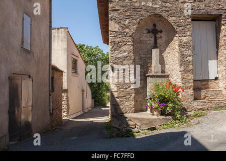 Crucifix shrine in wall alcove on village sidewalk - Stock Photo