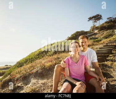Caucasian couple sitting on hillside - Stock Photo