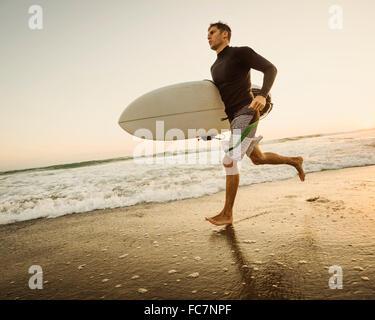 Caucasian man carrying surfboard on beach - Stock Photo