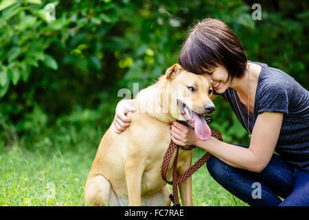 Caucasian woman petting dog in field - Stock Photo