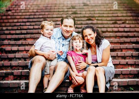 Caucasian family sitting on steps - Stock Photo