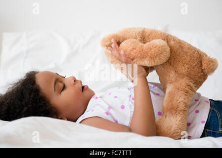 Mixed race girl playing with teddy bear - Stock Photo