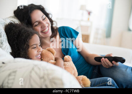 Mother and daughter watching television on sofa - Stock Photo