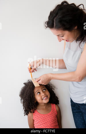 Mother measuring height of daughter against wall - Stock Photo