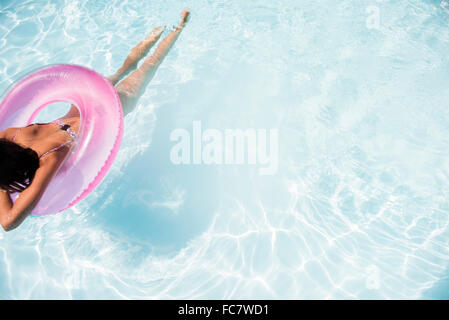Caucasian woman floating in swimming pool - Stock Photo