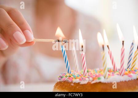Hispanic woman lighting birthday candles - Stock Photo